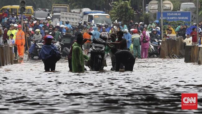 Banjir yang mengepung sejumlah wilayah di Bekasi tak hanya menerjang kawasan perumahan tapi juga di jalanan. Pengendara sepeda motor terpaksa diangkut gerobak menembus banjir yang tak dapat dilalui kendaraan di bawah ruas Jalan Tol Bintara, Bekasi, Selasa (21/2). (CNN Indonesia/Safir Makki)