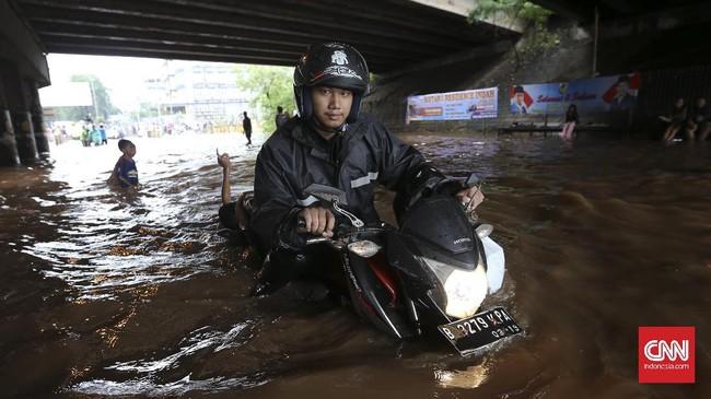 Tingginya genangan air tak membuat khawatir pengendara sepeda motor di bawah ruas Jalan Tol Bintara, Bekasi, Selasa (21/2). Sejumlah pengendara roda dua nekat menembus banjir dengan cara menuntun motornya meskipun berisiko membuat mesin kendaraannya mati karena businya terkena air. (CNN Indonesia/Safir Makki)