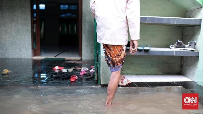 Selain rumah warga, jalan di depan musola yang berlokasi di Jalan Bina Warga kawasan Rawajati, Jakarta Selatan, juga terendam banjir sejak Selasa (21/2) pagi. Banjir yang menggenangi area rumah ibadah ini membuat warga yang hendak salat menjadi terganggu. (CNN Indonesia/Andry Novelino)