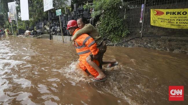 Seorang petugas proyek jalan tol di Bekasi membantu warga menembus banjir dengan cara digendong, Selasa (21/2). Bantuan ini sangat dibutuhkan terutama oleh warga yang berusia lanjut karena derasnya arus sangat membahayakan. Banjir yang mengepung sejumlah wilayah di Jakarta dan Bekasi merendamkan ribuan rumah. (CNN Indonesia/Safir Makki)