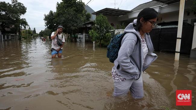 Selain ruas jalan, banjir juga menerjang kawasan permukiman penduduk seperti di Perumahan Pulo Permatasari, Bekasi Selatan, Selasa (21/2). Warga perumahan tersebut nekat menembus banjir agar bisa mencapai tujuan meskipun ketinggian air mencapai paha orang dewasa. (CNN Indonesia/Safir Makki)