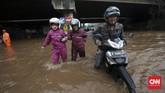 Tak sedikit pengendara sepeda motor yang nekat menembus banjir yang tidak dapat dilalui kendaraan roda dua di bawah ruas Jalan Tol Bintara, Bekasi, Selasa (21/2). Tingginya genangan yang mencapai selutut orang dewasa membuat mesin-mesin sepeda motor mati akibat busi basah. (CNN Indonesia/Safir Makki)