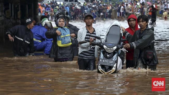 Arus lalu lintas terputus akibat banjir di bawah ruas Jalan Tol Bintara, Bekasi, Selasa (21/2). Warga membantu pengendara sepeda motor dengan menggunakan gerobak untuk bisa menembus banjir yang tak dapat dilalui kendaraan di bawah ruas tol tersebut. (CNN Indonesia/Safir Makki)
