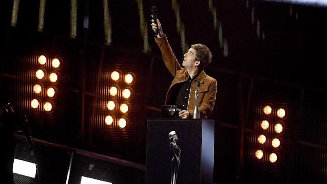 Noel Gallagher muncul kembali di tengah BRIT Awards, tanpa saudara sekaligus musuhnya, Liam. Hanya saja, ia tak tampil melainkan menjadi pembawa penghargaan. Ia membacakan kategori paling bergengsi, Album of The Year. <em>Blackstar</em> dari David Bowie yang menang. (REUTERS/Toby Melville)