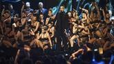 Robbie Williams menggebrak panggung bukan hanya dengan penampilannya sebagai penyanyi solo. Ia membawa seabrek penari berbusana seksi. Mereka meliukkan tubuh seksinya mengelilingi Williams. Sayang, aksi itu sempat diwarnai adegan mikrofon dan penari jatuh. (REUTERS/Toby Melville)