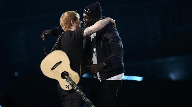 Ed Sheeran juga tampil, bersama artis hip hop Stormzy. Ia menampilkan lagu barunya, <em>Shape of You</em> yang benar-benar memamerkan keahliannya bermusik. Seperti biasa, Sheeran tampil bersama gitarnya. Penggemar di media sosial menyebut penampilan itu 'gila.' (REUTERS/Toby Melville)