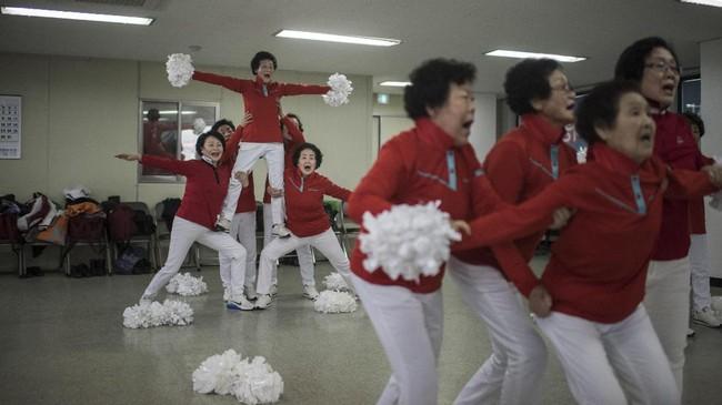 Cheer Mommy, grup pemandu sorak lansia umur75 tahun sedang melakukan latihan rutin dengan seragam merah-putih dan pom-pom putihnya di Samcheok, Pantai Timur Laut Korea Selatan, Jumat (AFP PHOTO / Ed JONES)