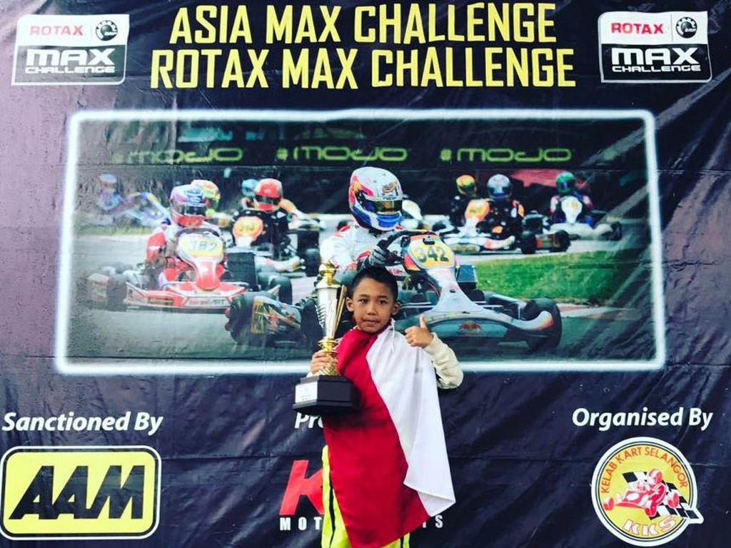 Aditya menunjukkan trofi juara pertama kelas Micro Max. Prestasi ini mengulang pencapaiannya pada Invitation Rotax Januari lalu di sirkuit yang sama. Saat itu, Aditya juga menyabet trofi juara pertama.