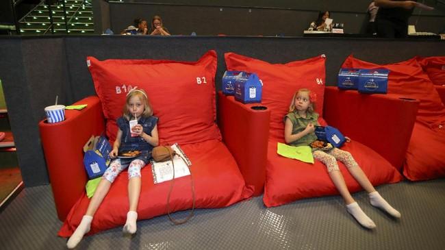 <p>Salah satu yang membuat menonton di bioskop ini terasa nyaman adalah adanya kursi beanbag seperti yang diduduki dua gadis ini. (REUTERS/Mike Blake)</p>
