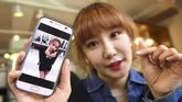 <p>Salah satu anggota lainnya, Jung Hye-Yoon (Ga-Bin) menunjukkan foto dia sebelum melakukan operasi plastik di Seoul, Korea Selatan. (AFP PHOTO / JUNG Yeon-Je)</p>
