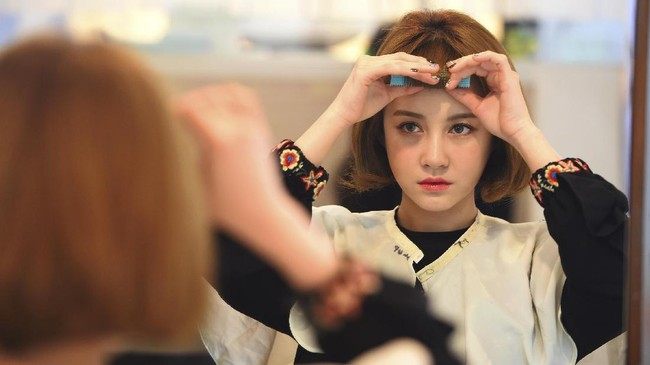 <p>Salah satu anggota girlband SixBomb, Kim Da-Young (Da-In) menunjukkan hasil operasi plastiknya pada 16 Maret lalu. Da-In melakukan perubahan di bagian wajah. (AFP PHOTO / JUNG Yeon-Je)</p>