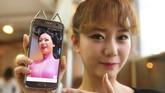 <p>Anggotaa SixBomb, Hong Hye-Jin (So-Ah) menunjukkan foto sebelum melakukan operasi plastik. Selain wajah, bagian lain yang ingin diubah adalah payudara. (AFP PHOTO / JUNG Yeon-Je)</p>