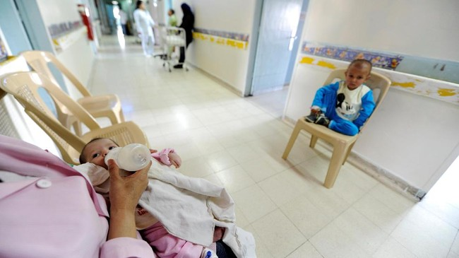 <p>Seorang suster memberi makan seoran bayi yang sedang menjalani tes kanker, sementara pasien anak lainnya duduk di kursi menunggu gilirannya untuk menerima pengobatan kankernya. (REUTERS/Omar Sanadiki)</p>