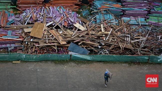 <p>Pekerja mengumpulkan sampah partisi di area proyek renovasi SUGBK. Tumpukan kayu ini berasal dari badan bangku-bangku di tribun bagian atas. (CNN Indonesia/Adhi Wicaksono.)</p>