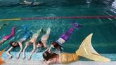 Tingkah polah perempuan-perempuan ini benar-benar tampak seperti putri duyung. Di pinggiran kolam renang dengan gaya bertelengkup, satu sama lain saling bercanda dan tertawa. (AFP PHOTO / Natalia Kolesnikova)