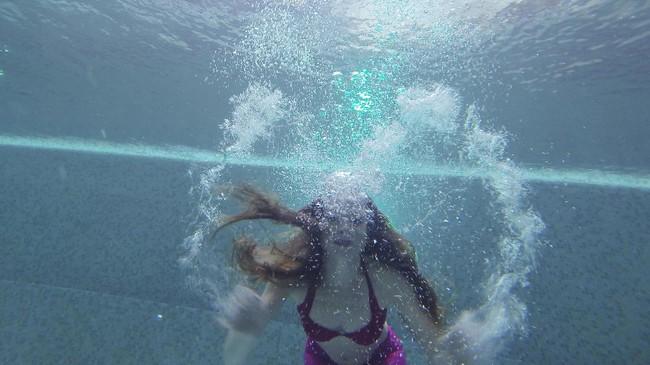 Seorang perenang menyempatkan membuat variasi gerakan-gerakan tangan di dalam air yang dianggap bisa menarik perhatian kamera yang membidiknya. Dengan berpose seperti ini bisa menghasilkan gambar yang apik. (AFP PHOTO / Natalia Kolesnikova)