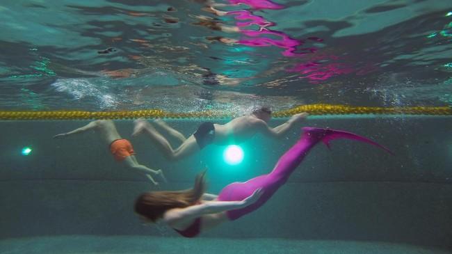 Di antara mereka sudah memimpikan menjadi putri duyung sejak kecil. Berenang dengan memakai kostum putri duyung selain bisa mewujudkan fantasi, juga mendapat kebugaran tubuh dengan gerakan-gerakan di dalam air dalam formasi yang menarik. (AFP PHOTO / Natalia Kolesnikova)
