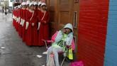 <p>Belasan wanita ini berpakaian seperti pembantu rumah tangga untuk mempromosikan serial Hulu, The Handmaid's Tale. Mereka berdiri di sebuah jalanan publik saat SXSW. (REUTERS/Brian Snyder)</p>