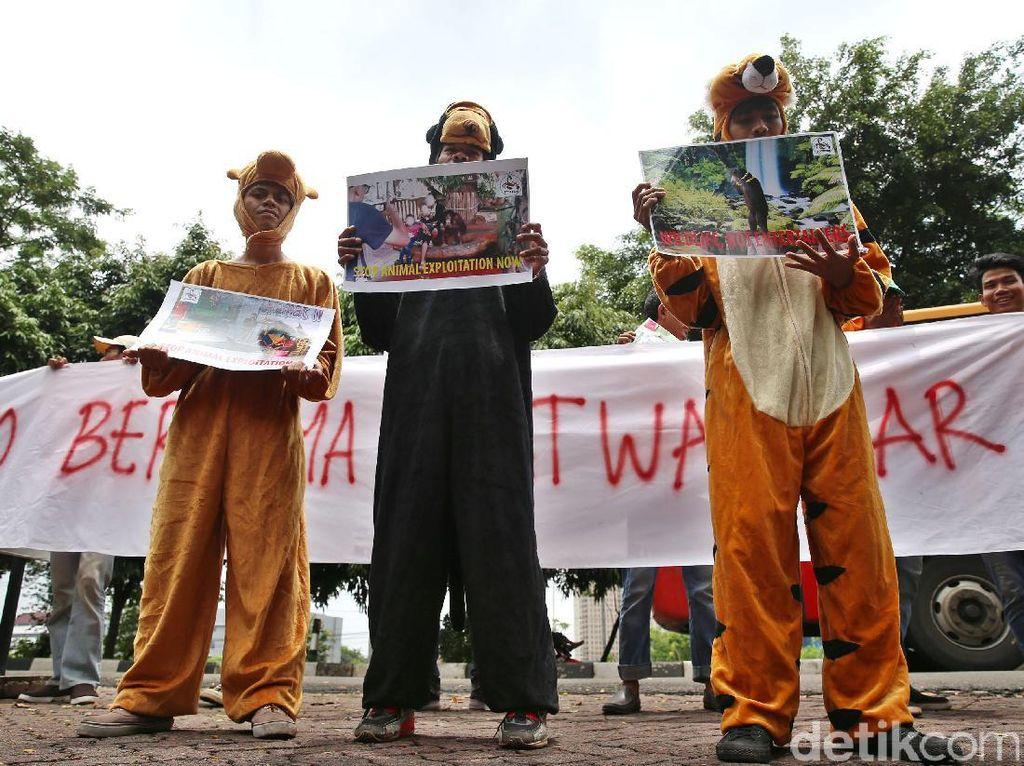 Tiga peserta aksi memakai kostum hewan. Mereka juga membentangkan poster.