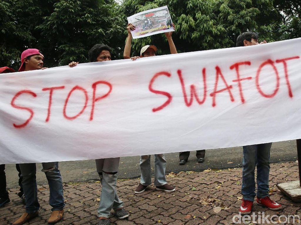 Para pecinta satwa membentangkan spanduk bertuliskan Stop Swafoto.
