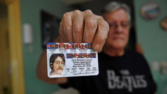 Mereka mencari namun tidak dapat dengan leluasa menunjukkan kebanggaan mereka terhadap the Beatles. Seperti seorang pria yang mengoleksi kartu mengemudi John Lennon ini. (AFP PHOTO / YAMIL LAGE)