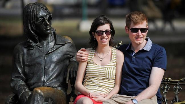 Sejumlah turis berpose di samping patung ikonik John Lennon di sebuah taman di kota Havana, Kuba. (AFP PHOTO / YAMIL LAGE)