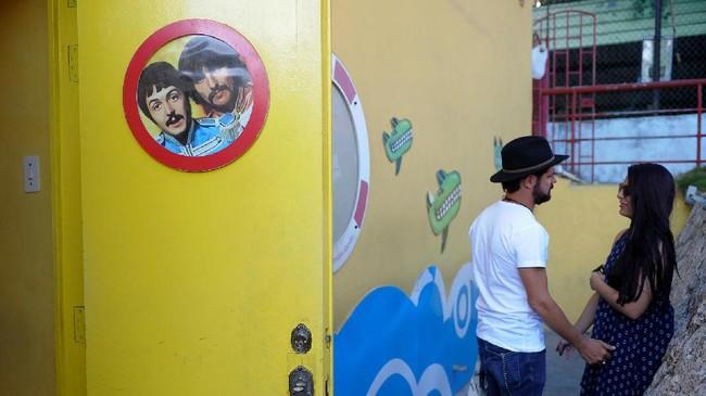 Sepasang penggemar the Beatles menunggu acara kumpul para penggemar band tersebut di the Yellow Submarine bar di Havana, 12 Maret 2017. (AFP PHOTO / YAMIL LAGE)
