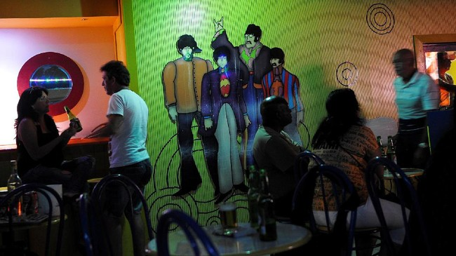 Para penggemar the Beatles menikmati minuman dan suasana the Yellow Submarine di Havana, Kuba. (AFP PHOTO / YAMIL LAGE)