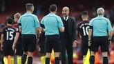 Manajer Manchester City Pep Guardiola berbicara dengan wasit Andre Marriner usai pertandingan di Stadion Emirates. Guardiola mengajukan sejumlah protes terhadap Marriner, terutama soal handball yang dilakukan bek Arsenal, Nacho Monreal. (Reuters / Eddie Keogh)