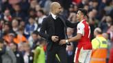 Pep Guardiola memeluk winger Arsenal, Alexis Sanchez, usai pertandingan. Guardiola pernah melatih pemain timnas Chile itu ketika saat menangani Barcelona.(Reuters / Eddie Keogh)