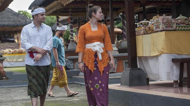 Bukan cuma warga lokal, namun wisatawan mancanegara juga ikut mengenakan pakaian adat ketika melihat perayaan Hari Raya Galungan di Pura Dalem Peliatan, Ubud, Bali, Rabu (5/4). Hari Raya Galungan akan disusul dengan Hari Raya Kuningan sepuluh hari kemudian, atau jatuh pada 15 April. (ANTARA FOTO/Nyoman Budhiana/Spt/17).