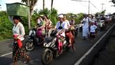 Para wanita dengan mengenakan busana adat Bali menjunjung sajen didampingi suami atau anak mereka menuju pura untuk melakukan persembahyangan. Suasana Denpasar dan daerah lain di Bali cukup semarak dengan penjor sebagai lambang kemakmuran.(AFP PHOTO / SONNY TUMBELAKA)