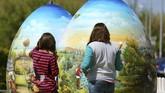 Dua anak perempuan memandang hiasan telur paskah setinggi dua meter diKoprivnica, Kroasia pada 9 April 2017. (REUTERS/Antonio Bronic)