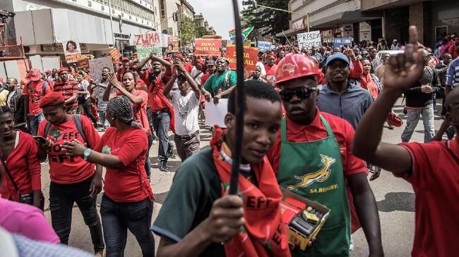 Protes yang dilakukan Rabu (12/4) itu bahkan jauh lebih besar dari sebelumnya. Sekitar 25 ribu orang melakukan long march untuk menuntut Zuma turun dari jabatannya. Mereka pun mengacungkan spanduk bertuliskan #ZumaMustFall.(AFP/GianluigiGuercia)
