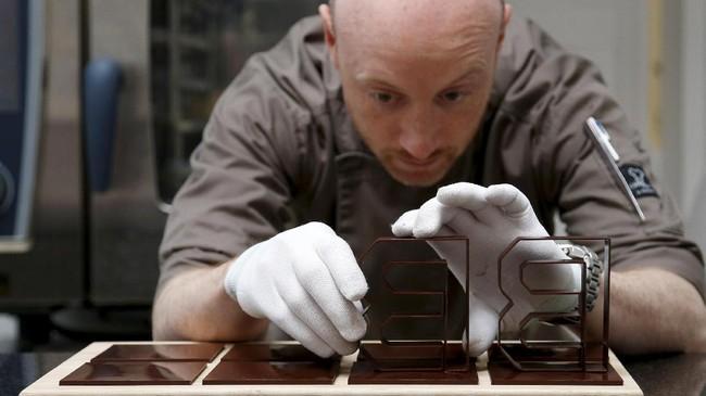 Proses pembuatan botol cokelat Bertinchamps membutuhkan waktu kurang dari 3 jam dan menggunakan 24.6 meter lempengan cokelat. Sedangkan, untuk logo dari cokelat, posisi harus diatur dengan sangat hati-hati agar tidak cepat meleleh dan berubah bentuk. (REUTERS/Francois Lenoir)