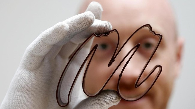 Gaetan Richard poses with the logo of the Miam Factory 3D printing chocolate company after being printed by a specialized 3D machine in Gembloux, Belgium, April 10, 2017. Picture taken April 10, 2017. REUTERS/Francois Lenoir