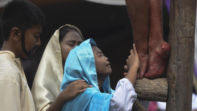 Para pemuda melakukan visualisasi jalan salib saat peringatan Jumat Agung di Gereja Katolik St Mikael, Surabaya, Jawa Timur, Jumat (14/4). ANTARA FOTO/Zabur Karuru.
