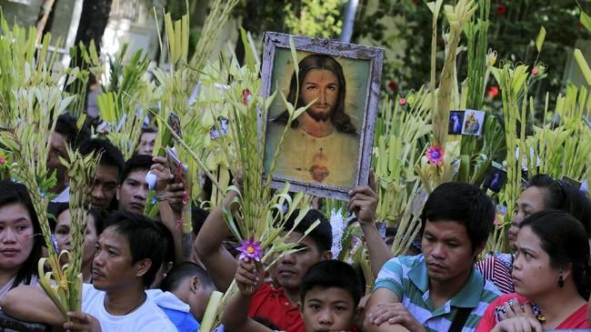 Seorang pria menjunjung gambar Yesus yang dikelilingi oleh hiasan dari pelepah daun kelapa sebagai bagian dari perayaan Pekan Suci di Manila, Filipina, 9 April 2017. (REUTERS/Romeo Ranoco)