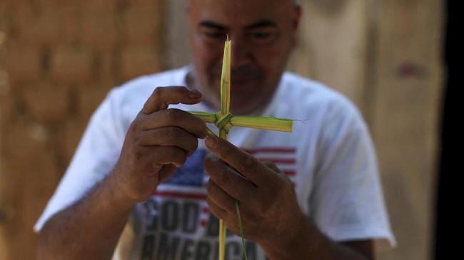 Di El Salvador, seorang pria membuat hiasan salib dari batang pohon palem menjelang prosesi Los Cristos, bagian dari perayaan Pekan Suci di negaranya, 13 April 2017.(REUTERS/Jose Cabezas).