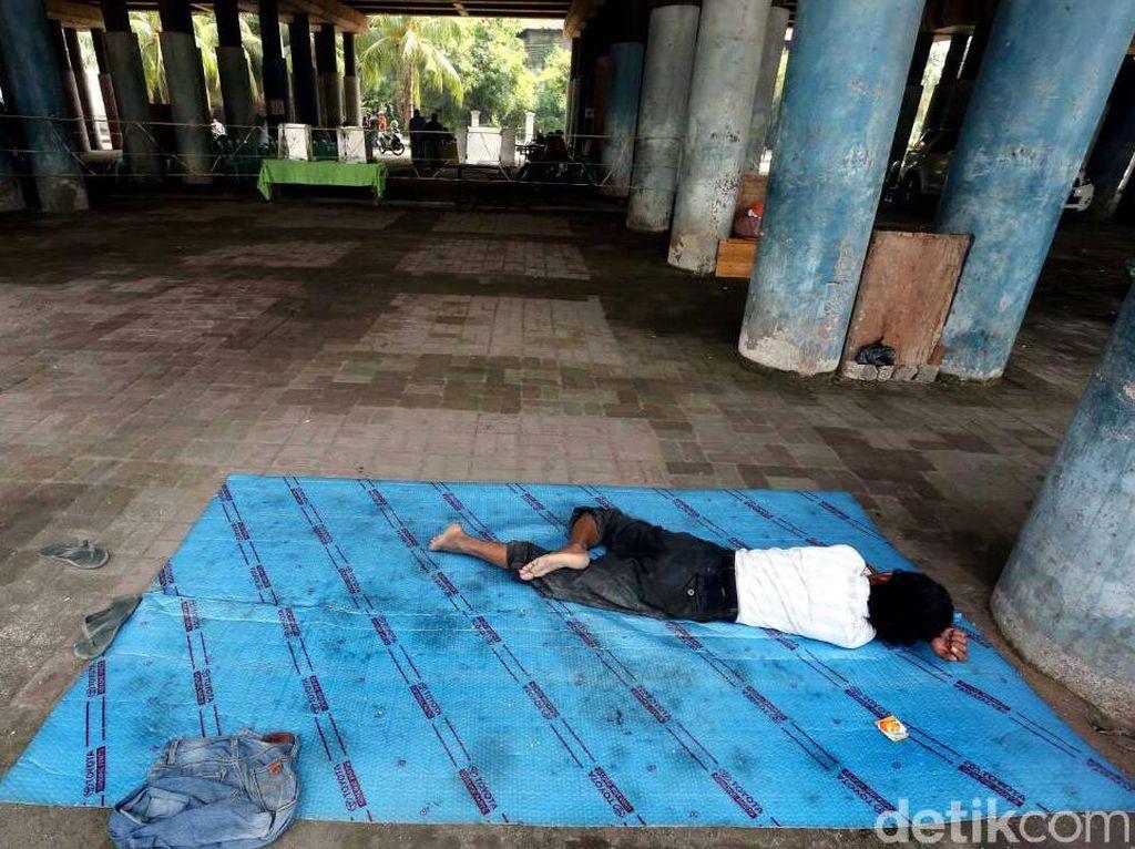 Seorang warga tertidur di dekat TPS.