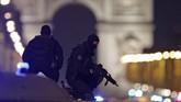 <p>Dalam beberapa cuplikan tayangan di televisi, ruas jalan Champs Elysees terlihat dipenuhi mobil polisi dan petugas bersenjata. (Reuters/Christian Hartmann)</p>