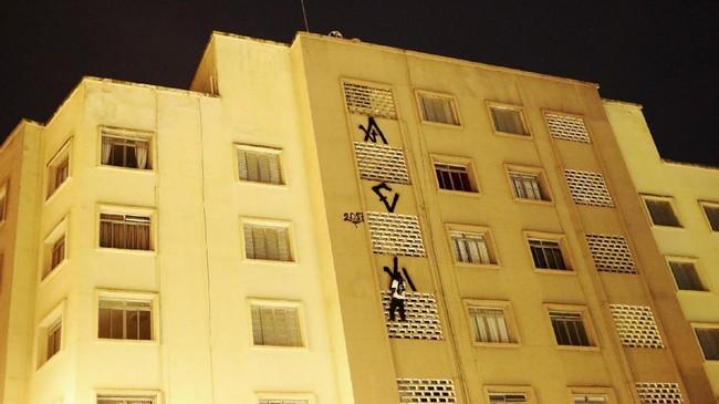 Tapi itu tidak menghalangi Pichadores menggambar simbol unik Pichacao yang berisi karakter huruf aneh, di dinding-dinding yang tersedia. Mereka bahkan berani naik ke puncak gedung untuk menorehkan simbol itu, seolah mengolok Doria. (REUTERS/Nacho Doce)