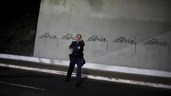 """Salah satu seniman jalanan lain, diketahui bernama Iaco bahkan berani menyemprotkan cat ke dinding yang baru saja dibersihkan, dan menulis: """"Doria"""" sampai tujuh kali. Dinding itu seakan penuh. Empat menit setelah ia melakukannya, polisi datang dengan borgol. (REUTERS/Nacho Doce)"""