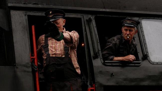 Masinis memberi salam menandai kereta api uap akan segera aktif dan beraksi dalam perayaan Steam Engine Parade. Setelah hampir dua dekade, gelaran ini juga masuk dalam agenda wisata yang menarik untuk dikunjungi saat berada di Polandia. (REUTERS/Kacper Pempel)