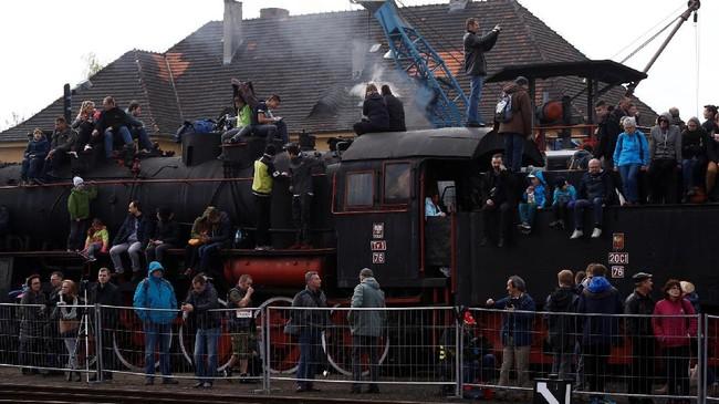Para pengunjung beramai-ramai menaiki kereta dan mengabadikan momen saat Steam Engine Parade berlangsung di Wolsztyn, Polandia. (REUTERS/Kacper Pempel)