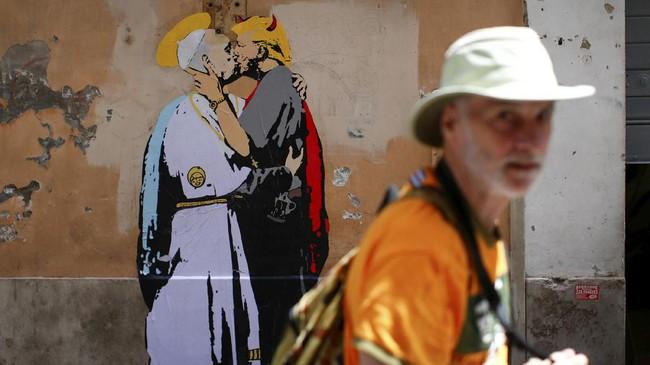 Mural tersebut juga dilampirkan sebuah tulisan berbunyi 'The Good Forgives the Evil' dan sebuah tanda tangan 'TVBoy' yang diyakini merujuk kepada seniman jalanan Salvatore Benintende. (REUTERS/Tony Gentile)