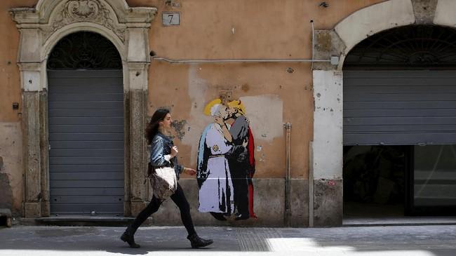 Mural itu menggambarkan Paus Fransiskus dengan salib di leher dan halo di kepala tengah memeluk Trump yang digambarkan dengan tanduk dan memiliki pistol. (REUTERS/Tony Gentile)
