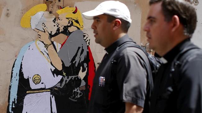 Mural tersebut dicat di atas kertas dan ditempel di dinding pada malam hari. Mural tersebut merupakan karya seniman jalanan sebagai respon sering munculnya sang Paus ke muka publik Roma dalam beberapa bulan terakhir. (REUTERS/Tony Gentile)