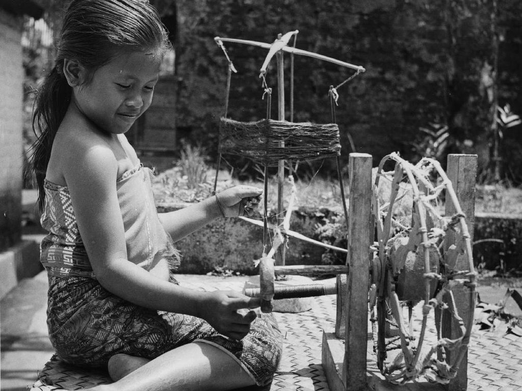 Seorang anak perempuan tengah memintal benang. Meski menggunakan alat sederhana tetapi kualitas benangnya sangat tinggi. Richard Harrington/Getty Images.