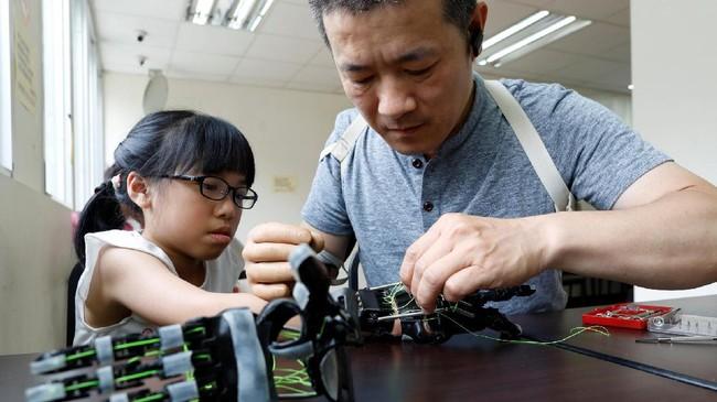 Chang mulai membuat lengan bionik untuk seorang gadis berusia 8 tahun, Angel Peng yang lumpuh akibat kecelakaan ketika ia berusia 9 bulan.(REUTERS/Tyrone Siu)